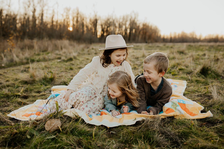 Three kids wrestling on blanket outside
