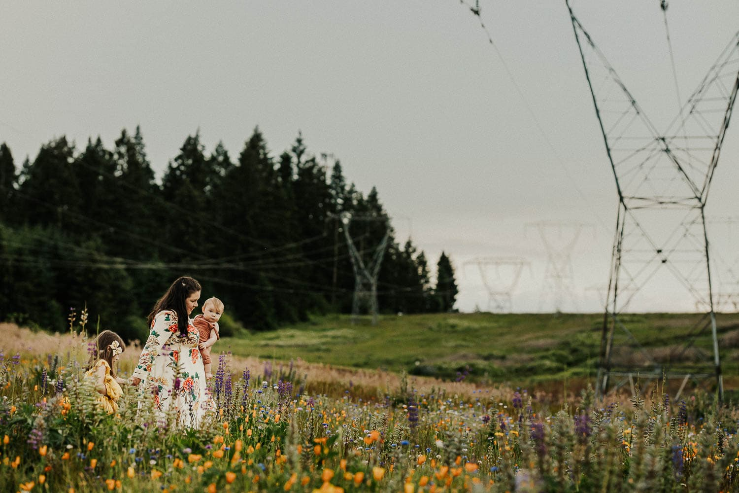 mommy and me session in portland flower fields - mom walking while holding one child and holding hand of the other