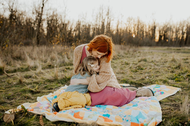 Mom cuddling daughter on a blanket