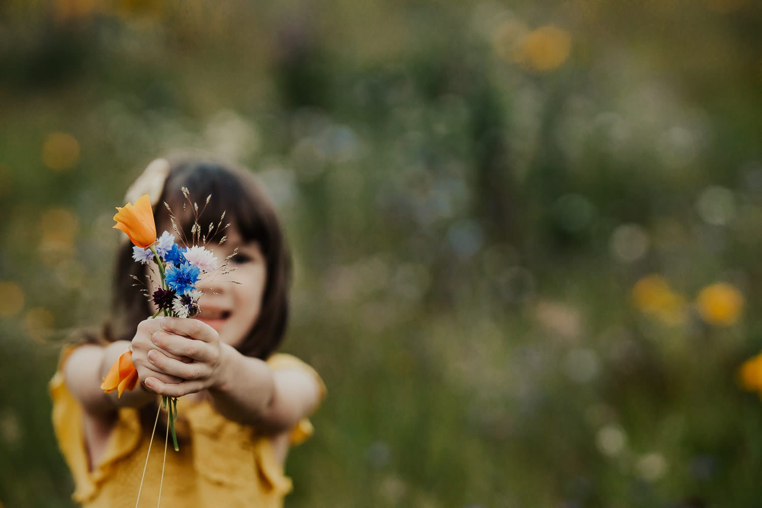little girl holding a bouquet of flowers up to the camers