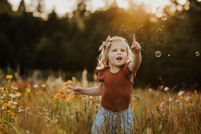 Little girl in a field of flowers popping a bubble - photos in flower fields