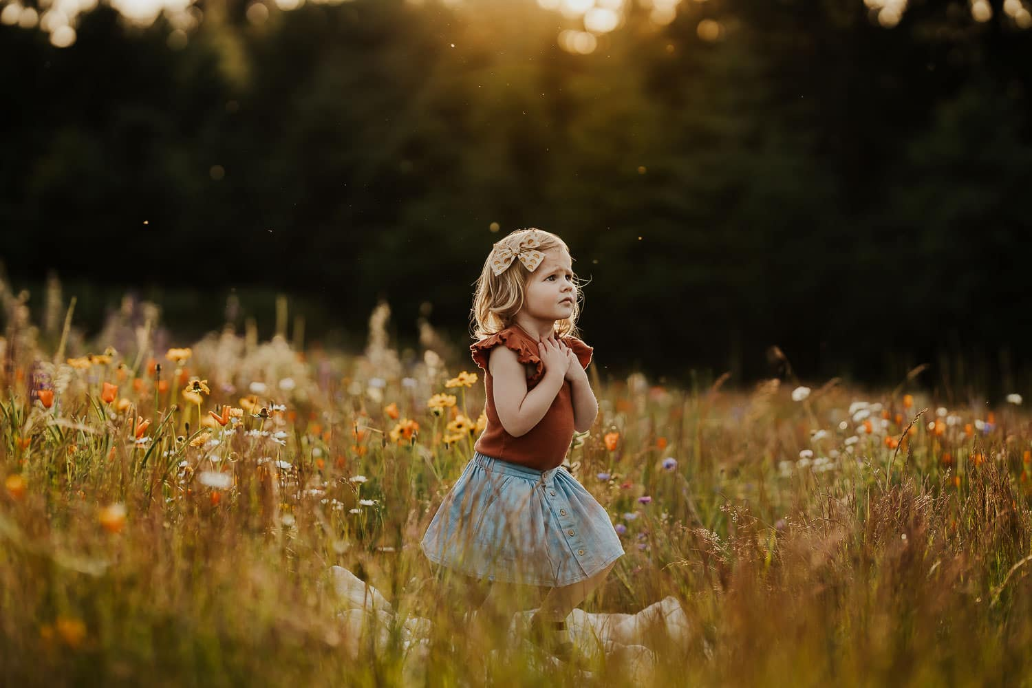 Little girl in a field of flowers with her hands on her heart