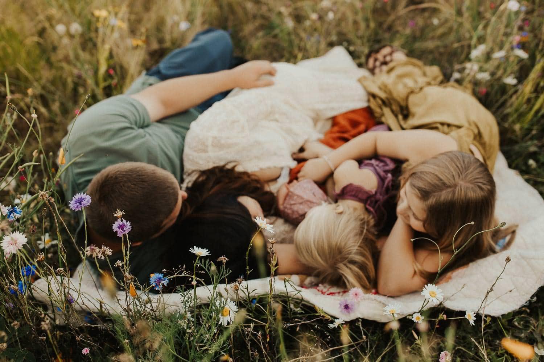 family laying down on a blanket in a flower fields near portland oregon