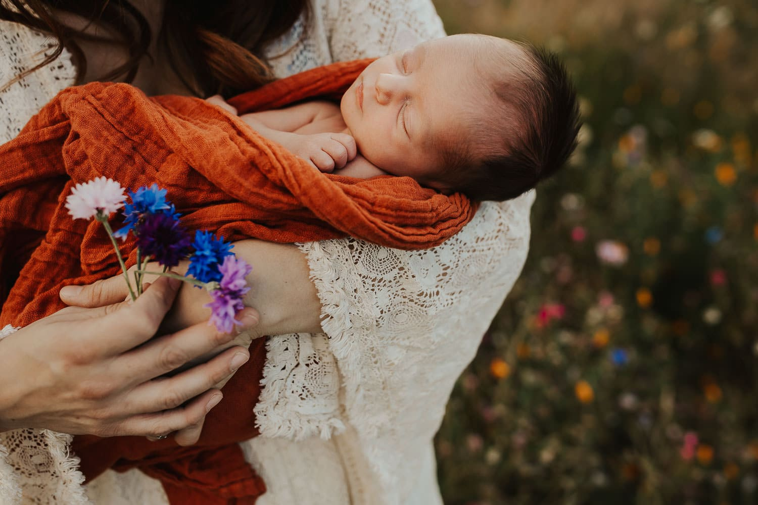 Closeup of newborn baby girl in moms harms with a bouquet of flowers
