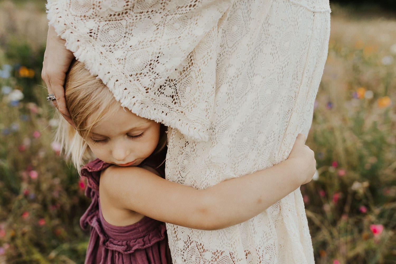 Little girl hugging her mom in a flower field near portland oregon