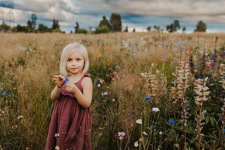 Adorable blonde girl in flowers near Portland Oregon