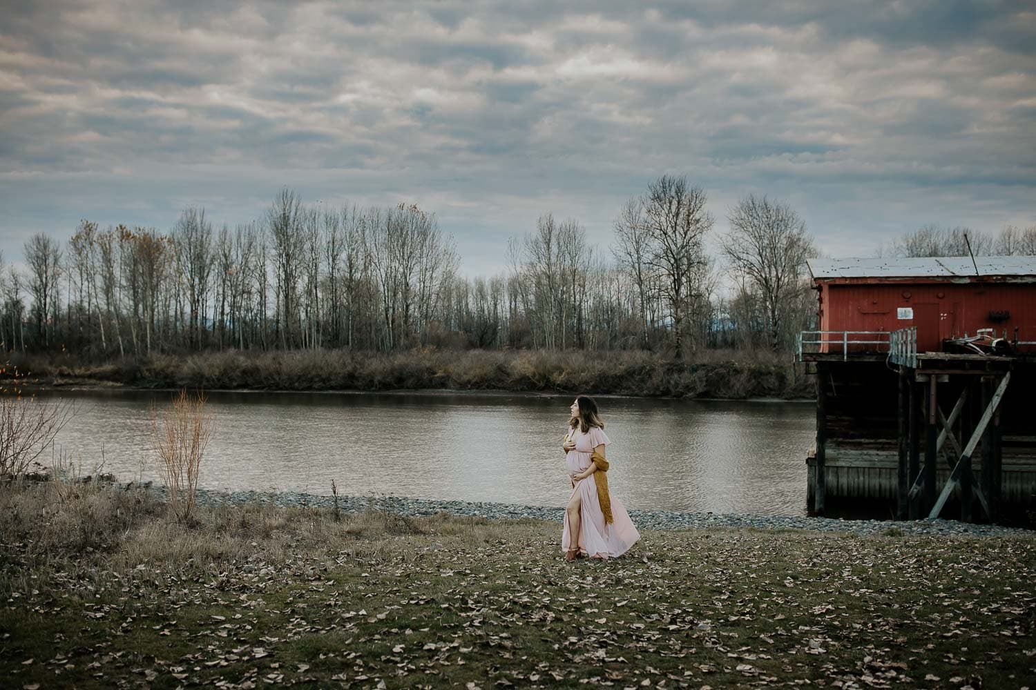 Maternity photos in the winter season - mom walking with river behind her