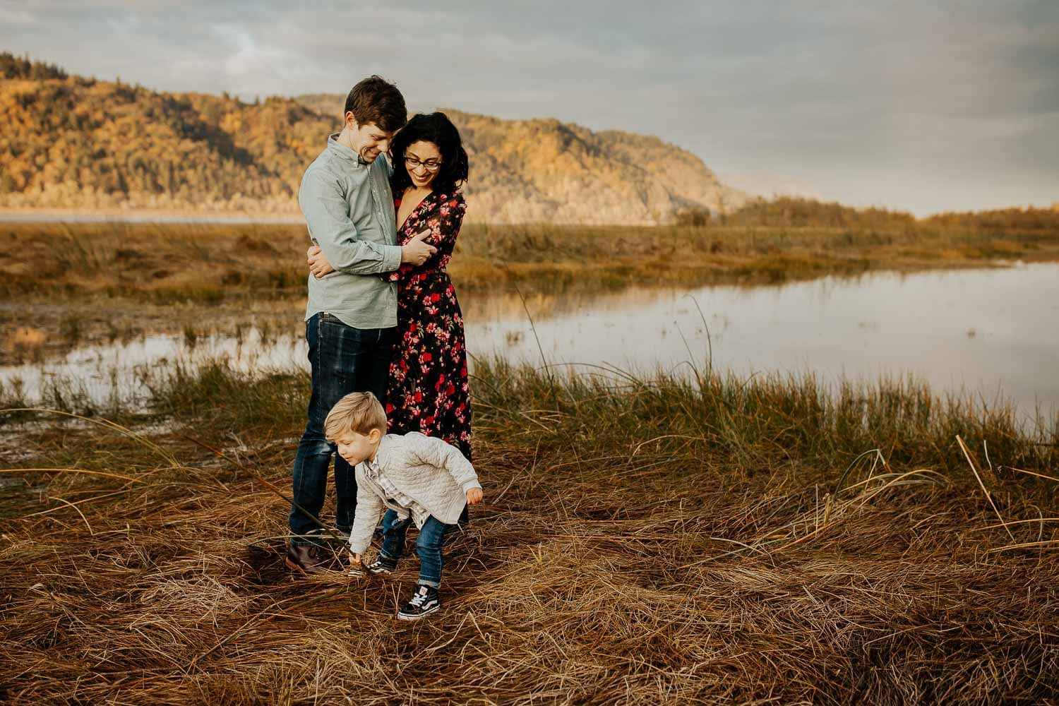 Mom, dad, and toddler in front of a puddle and mountain