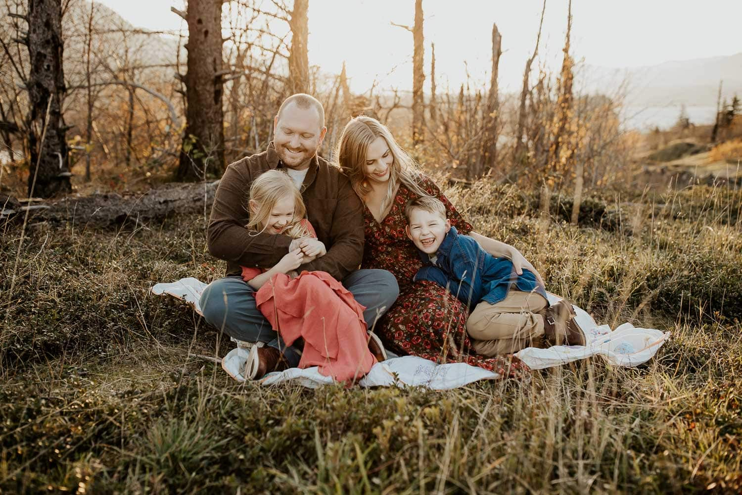 family of four cuddling on blanket with sun behind them - columbia river gorge family photos