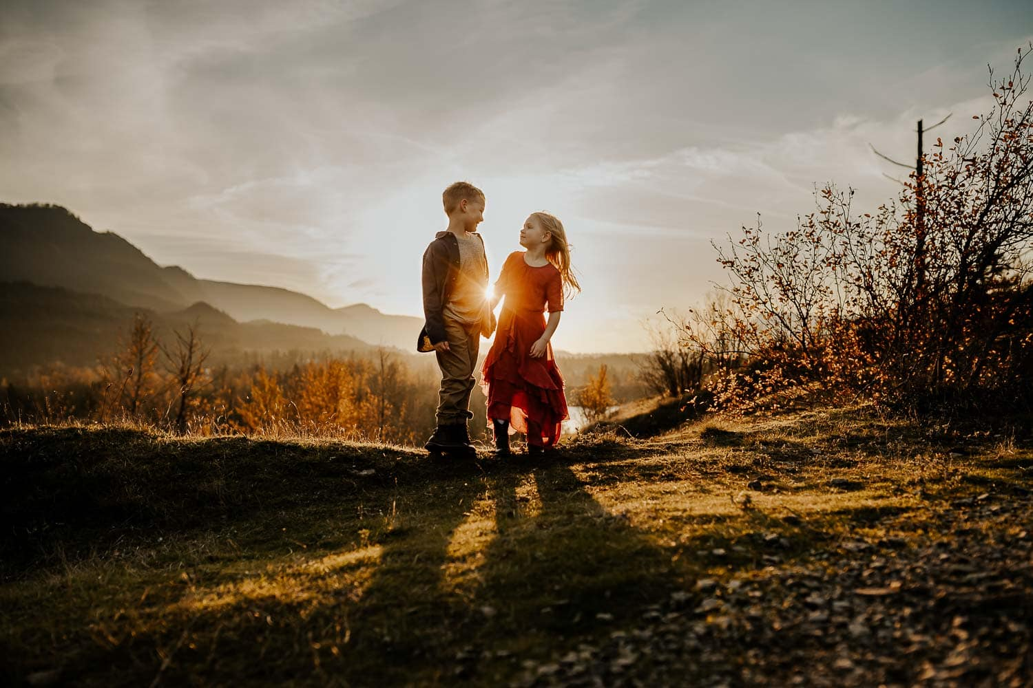 Kids holding hands with the sun shining in between them with a beautiful view behind them - family photos in the columbia gorge