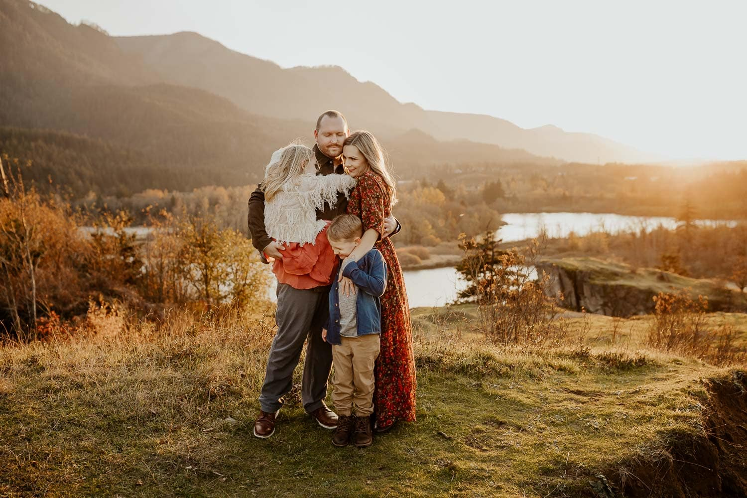 Family of four embracing with the columbia river gorge behind them - fall season