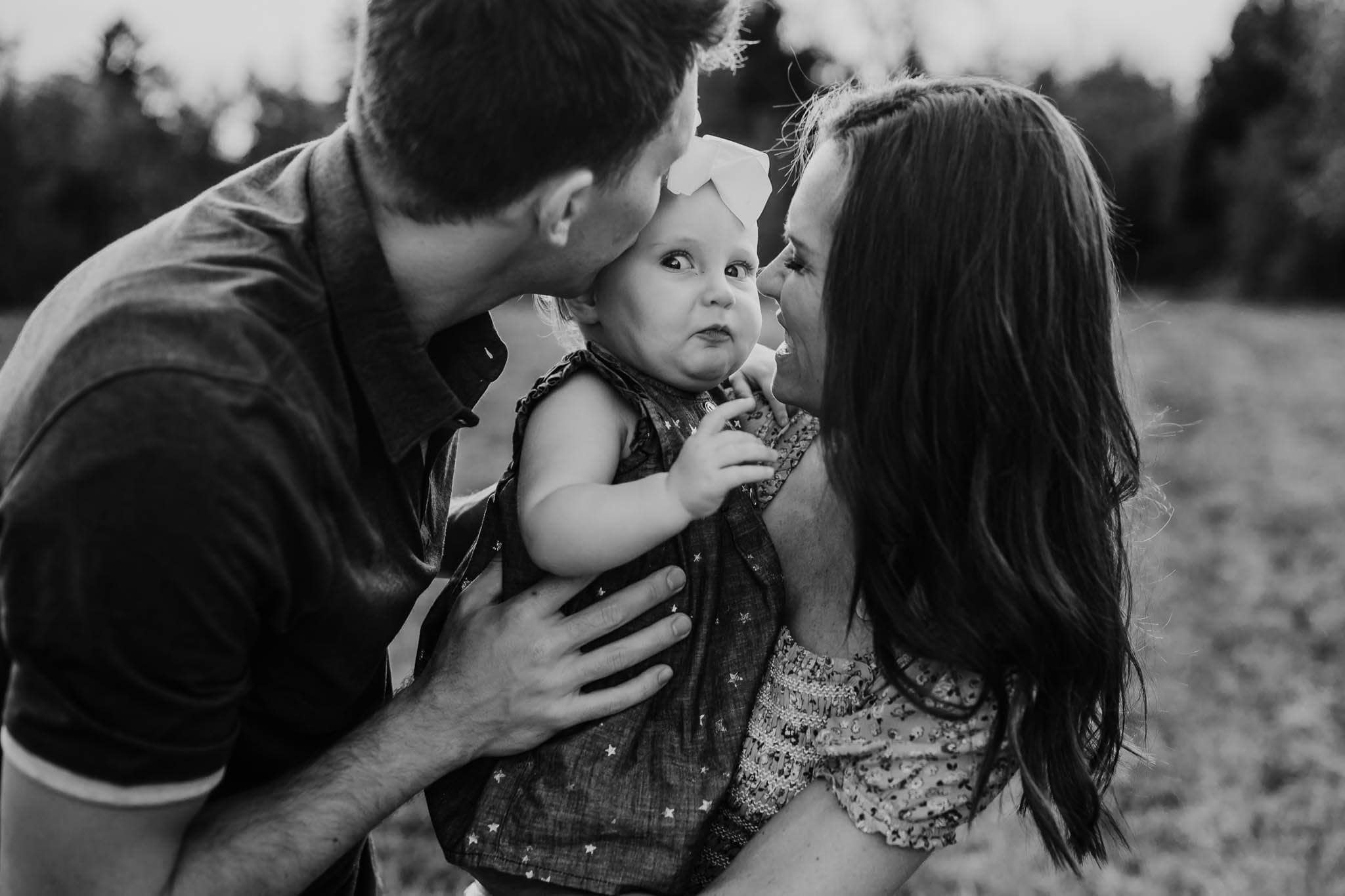 Parents holding toddler girl making funny face
