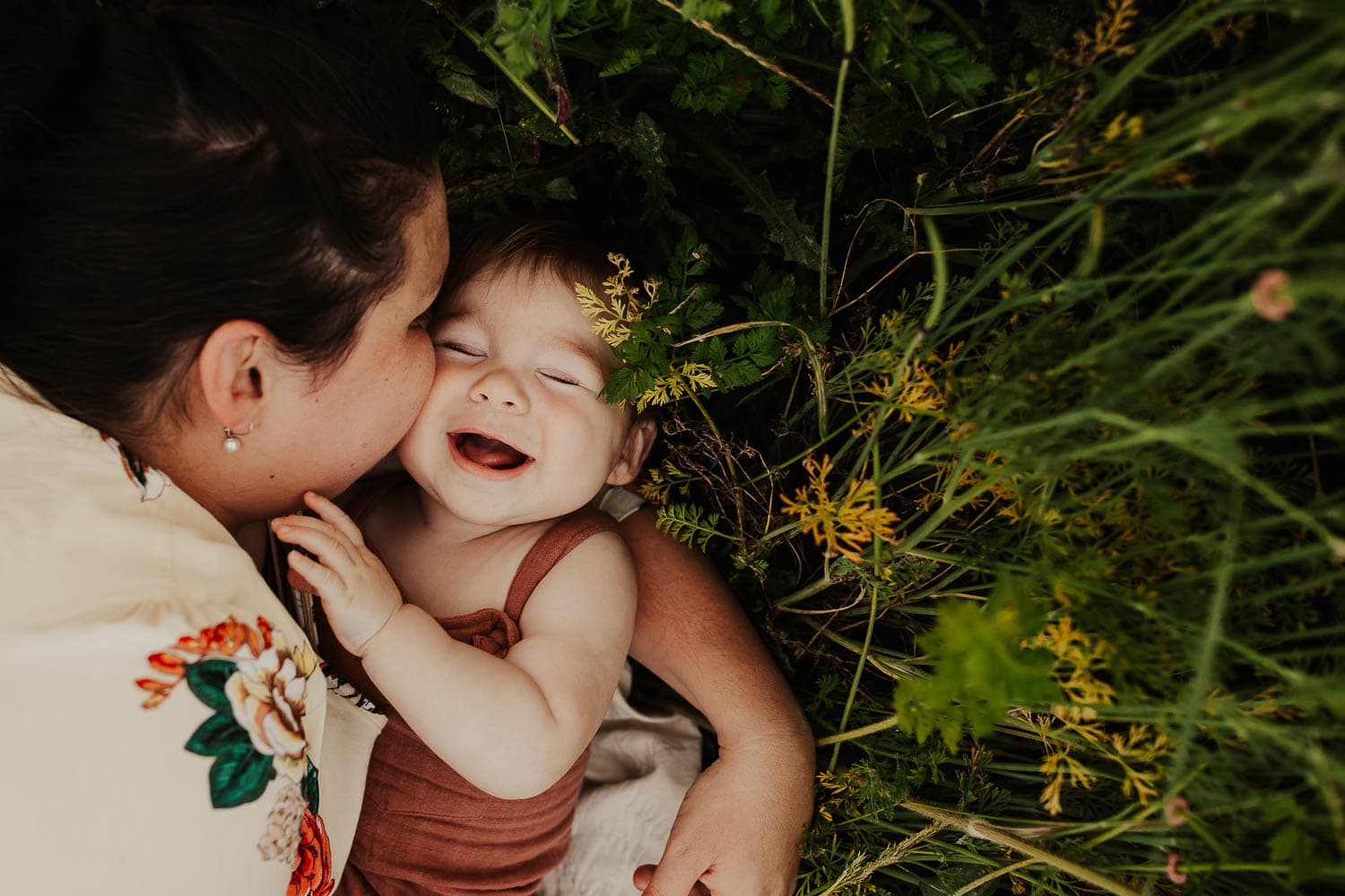 mom kissing baby's cheek while ha laughs - laying in tall green grass