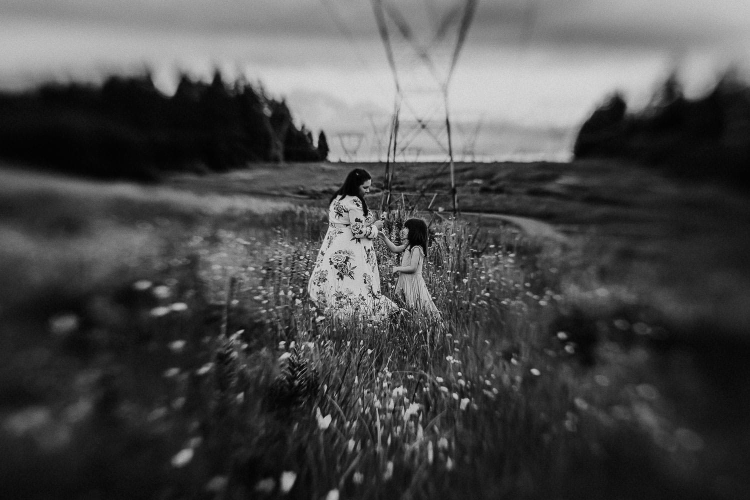 black and white photo of mom and daughter holing a flower near portland