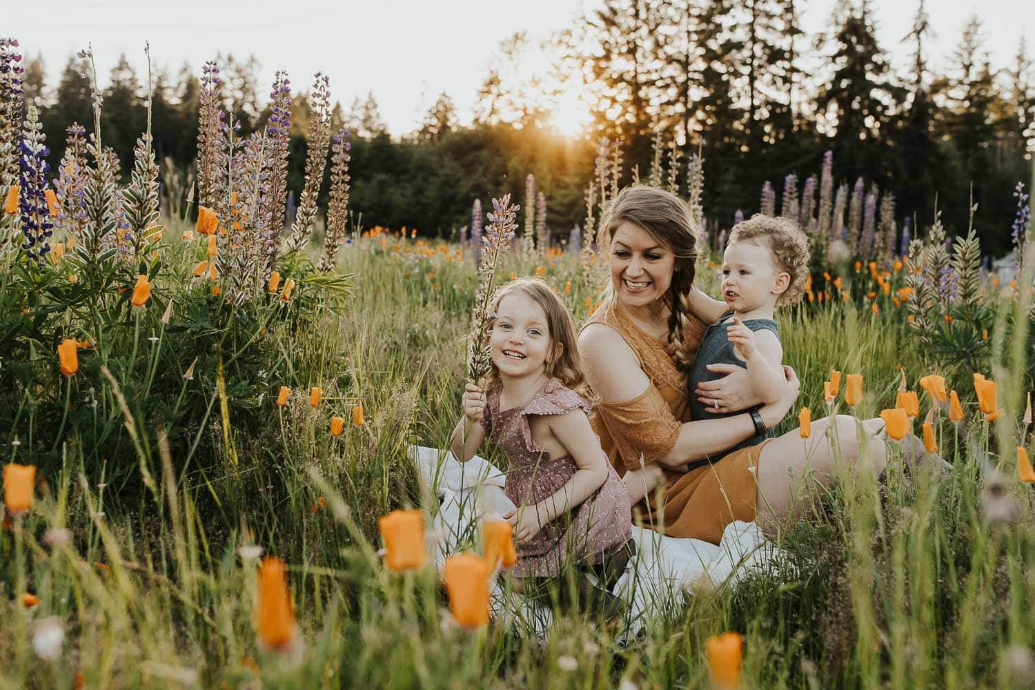 Mom and two kids sitting in flower field