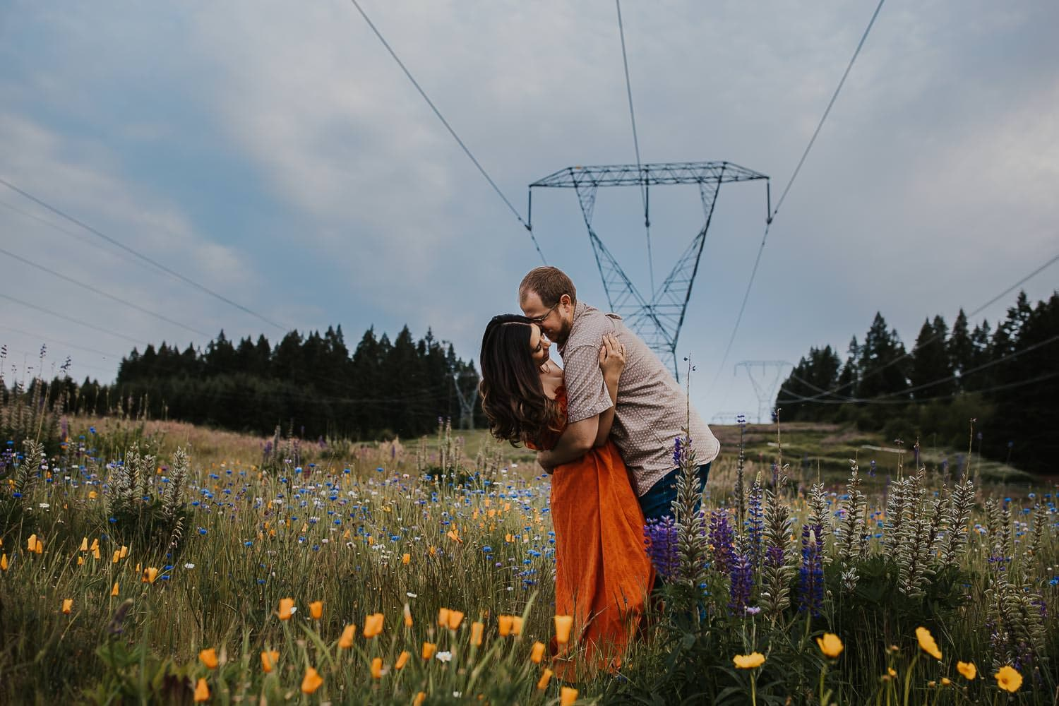 Couple dancing in a flower field with power lines behind them
