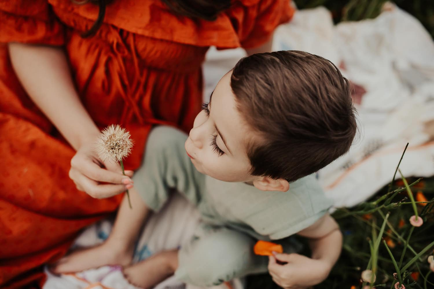 Little boy blowing on a dandelion flower with his mom