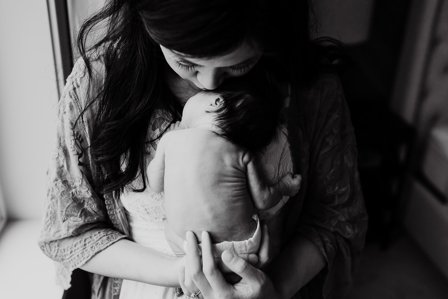 black and white photo of mom kissing her newborn baby by a window   starting a family photography business from scratch