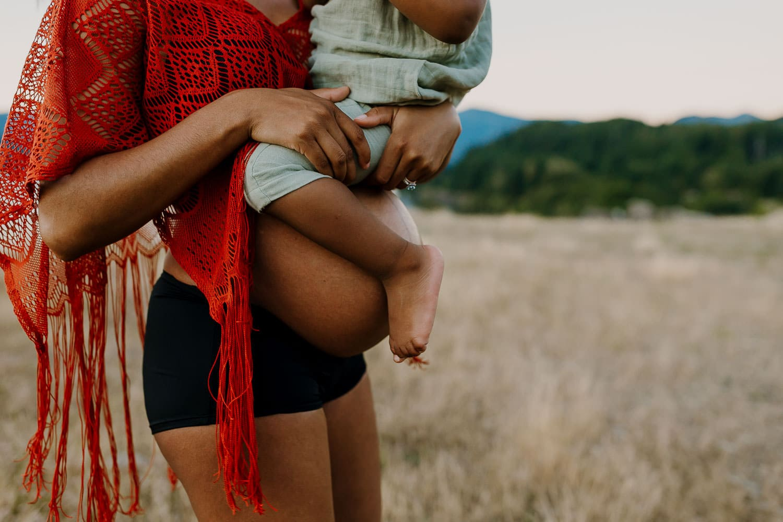 Pregnant mama in orange tassel top holding her toddler