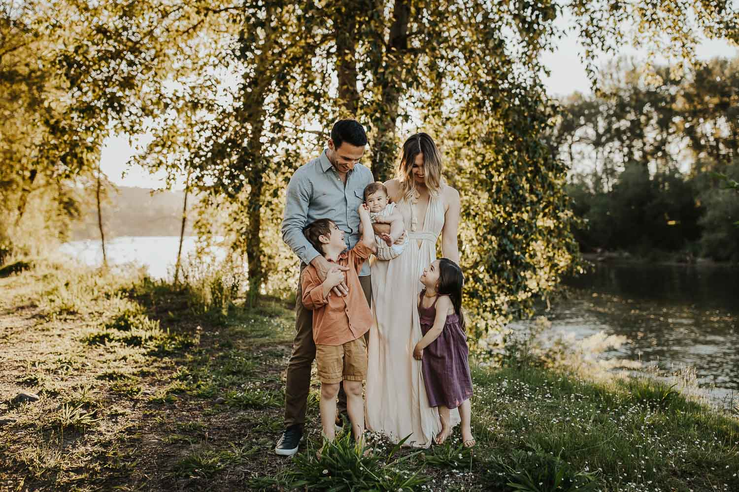 Family of five standing with greenery around them - what colors to wear for family photos