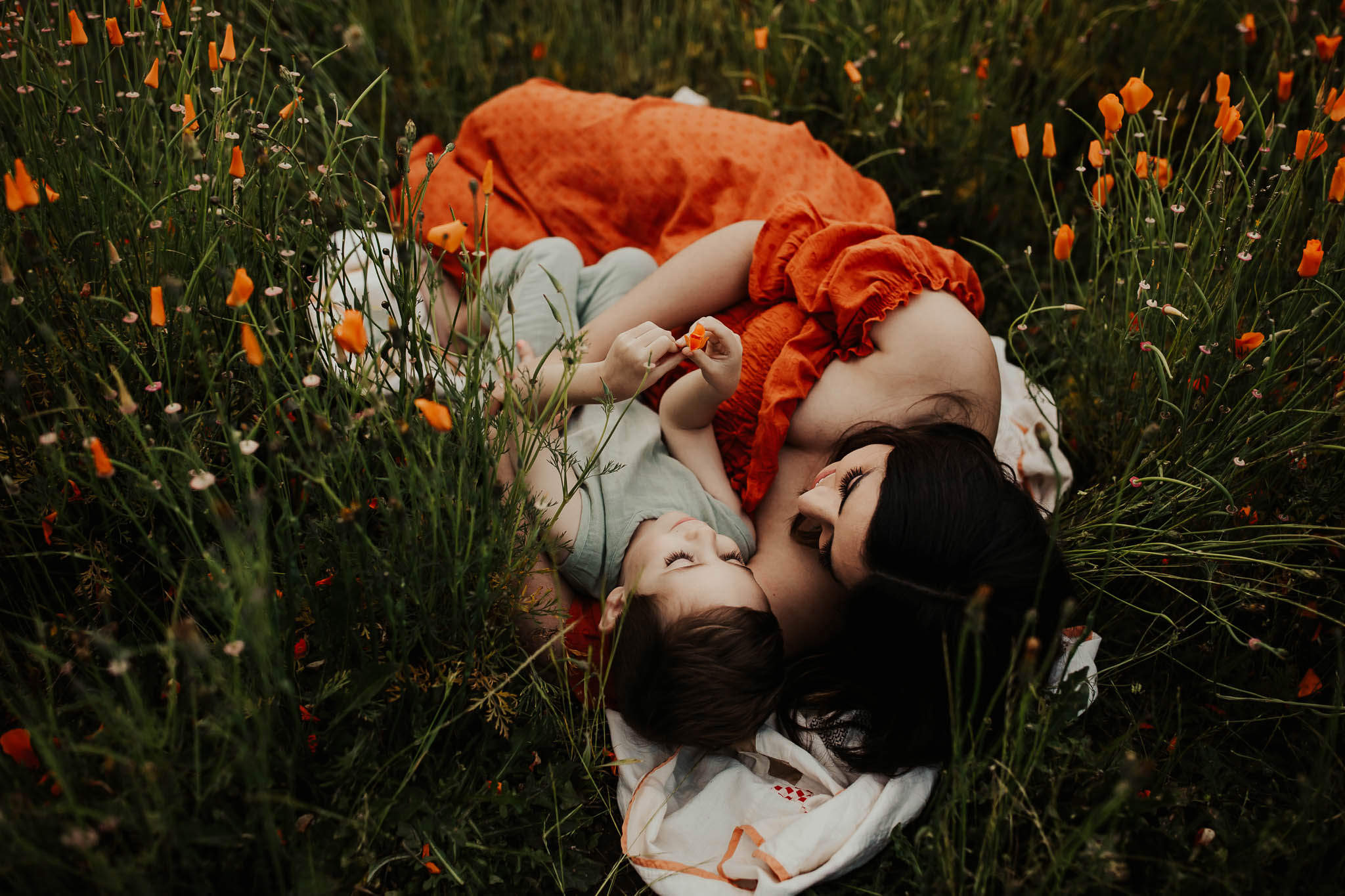 Mom and son laying on blanket in orange poppies