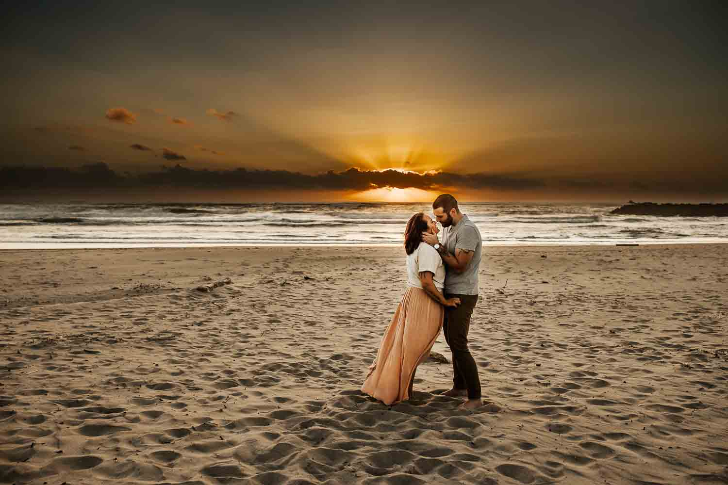 best locations for couples photography near Portland oregon- couple on the beach with the sun setting behind them - amazing sunset