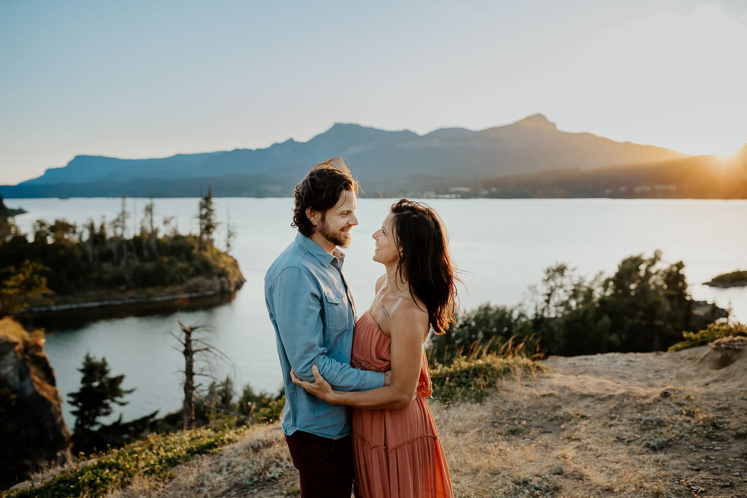 couple holding each other with river behind them near portland oregon