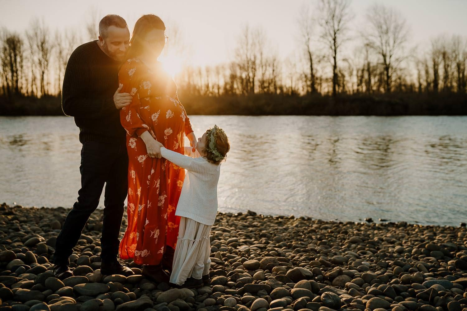 maternity photo of family by a river at sunset   how to start a photography business