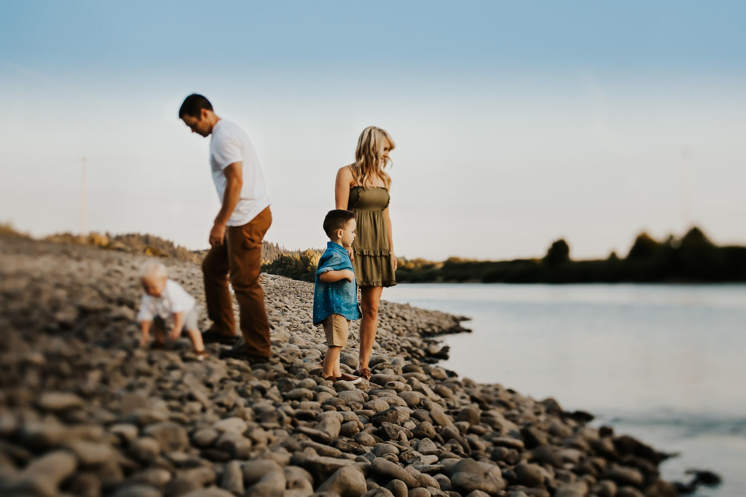Portrait of a family of four playing near a river throwing rocks into the water near portland oregon
