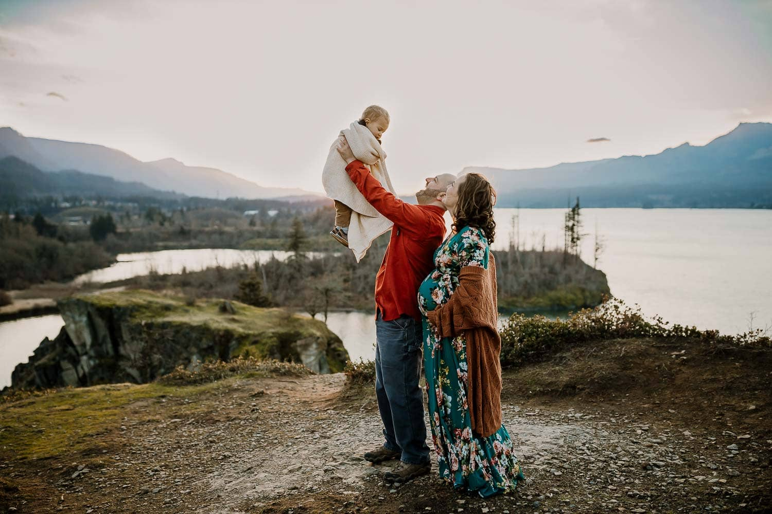 family maternity photo of dad lifting toddler in the air while pregnant mama watches them