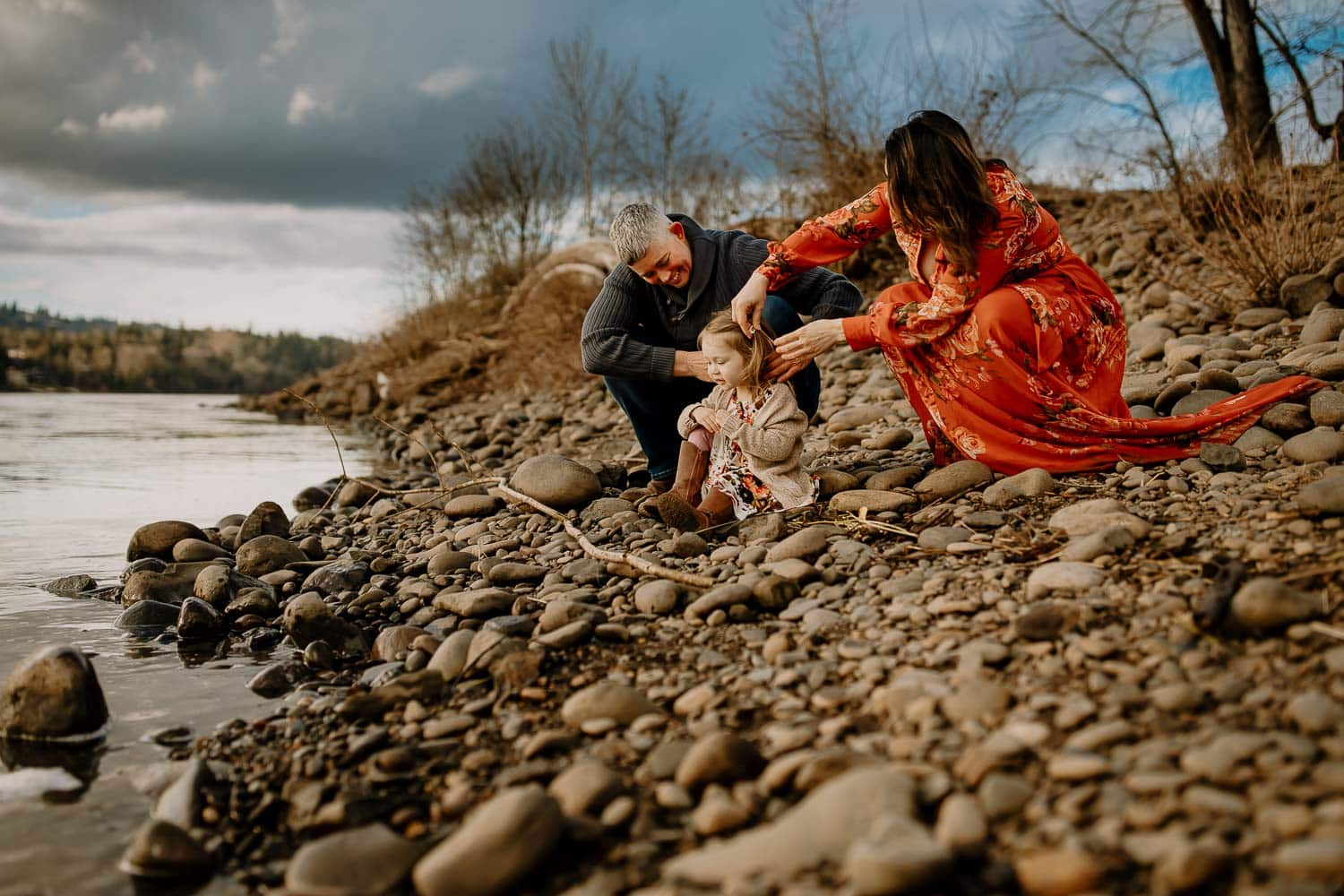 family of three sitting on rocks near a river, mom putting clip in toddlers hair