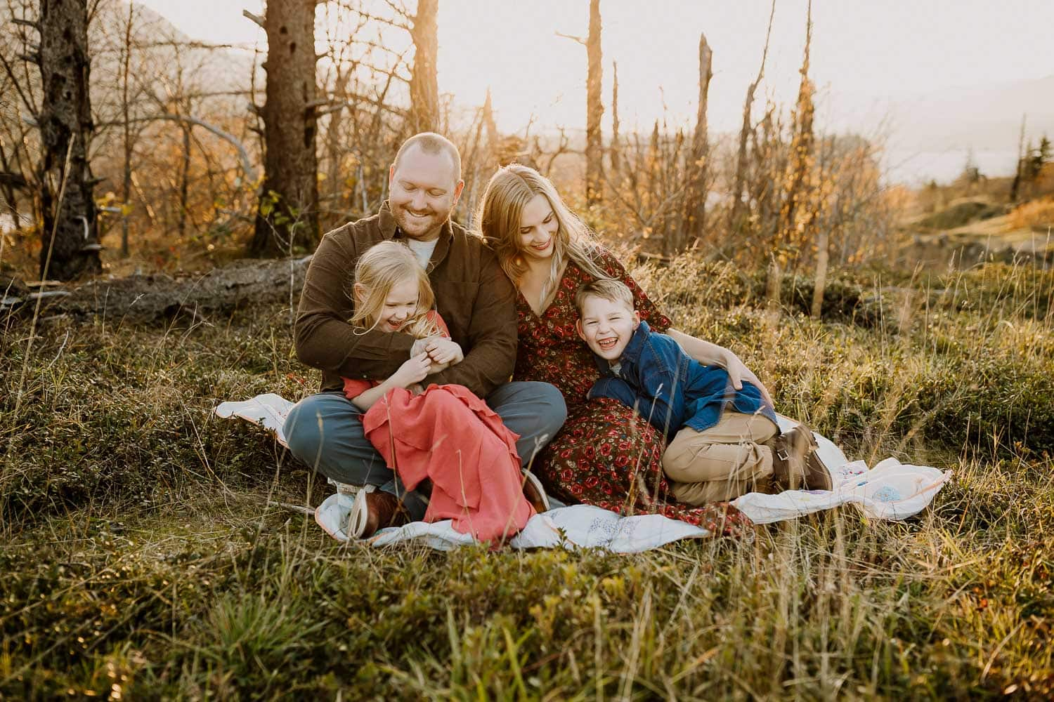 Family tickling and laughing on a blanket during their lifestyle family photo session in Portland Oregon
