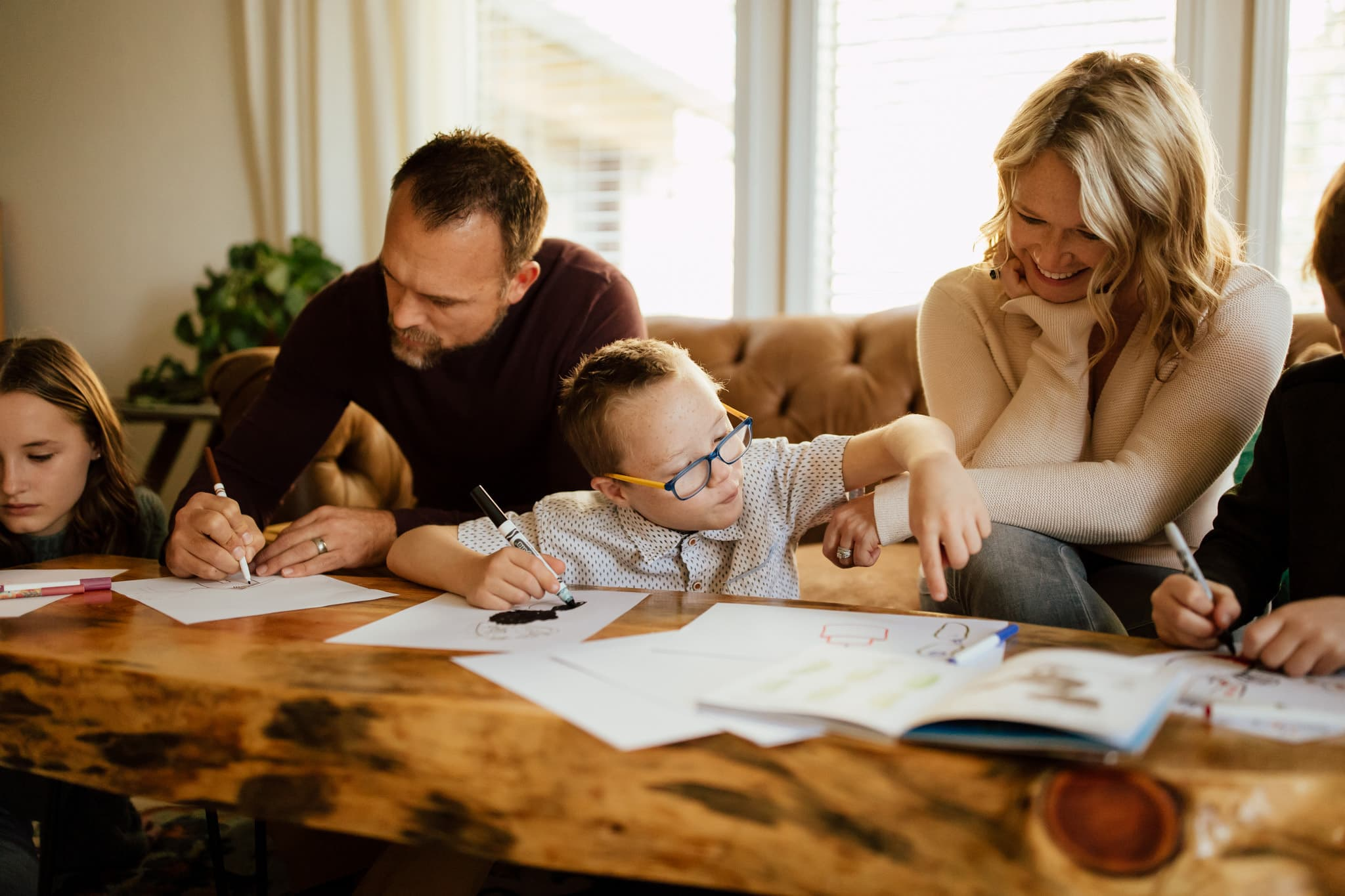 Little boy doing crafts at the table with family - what to do at home