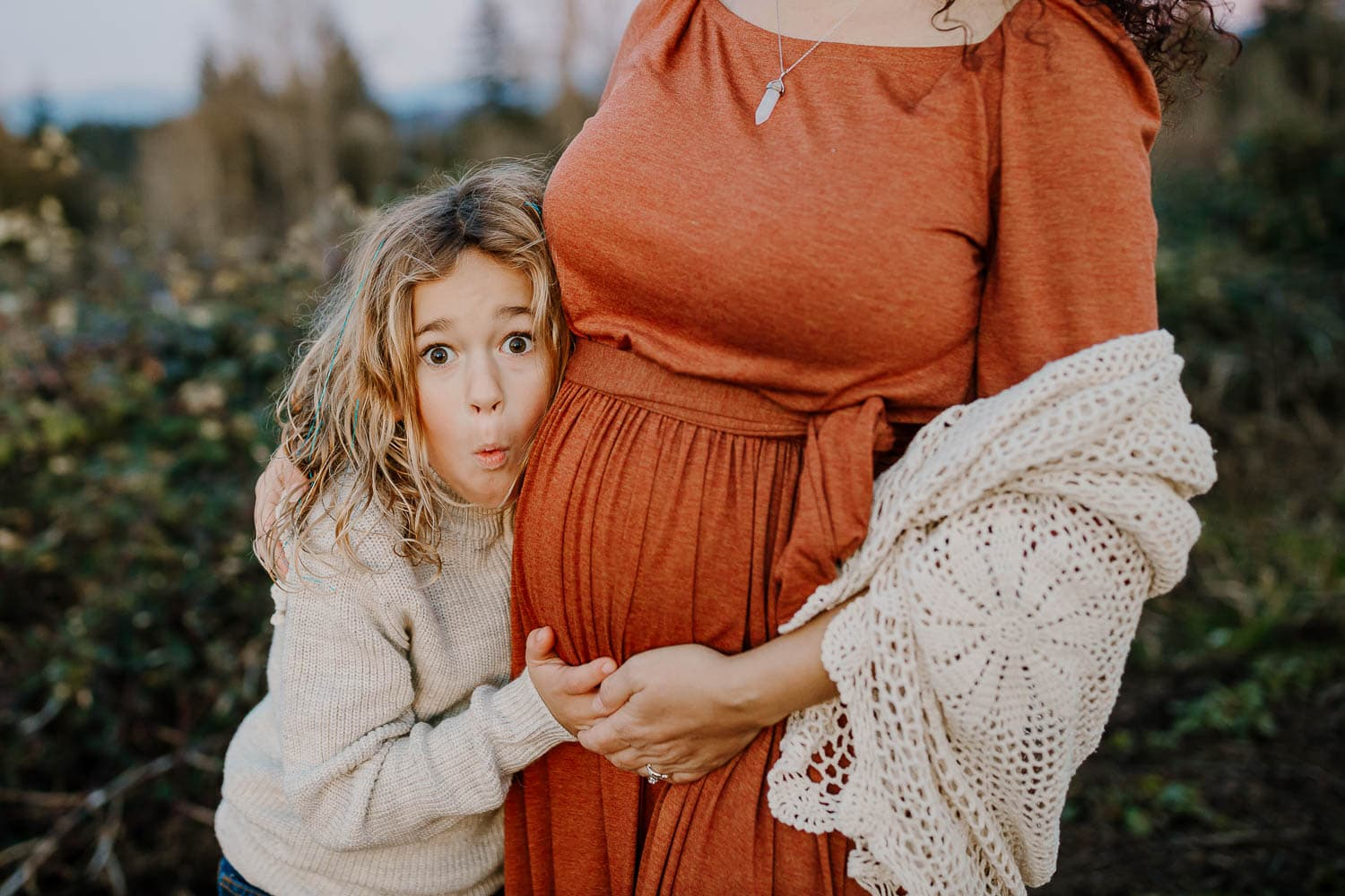 Little boy making a funny face next to his mom's pregnant belly
