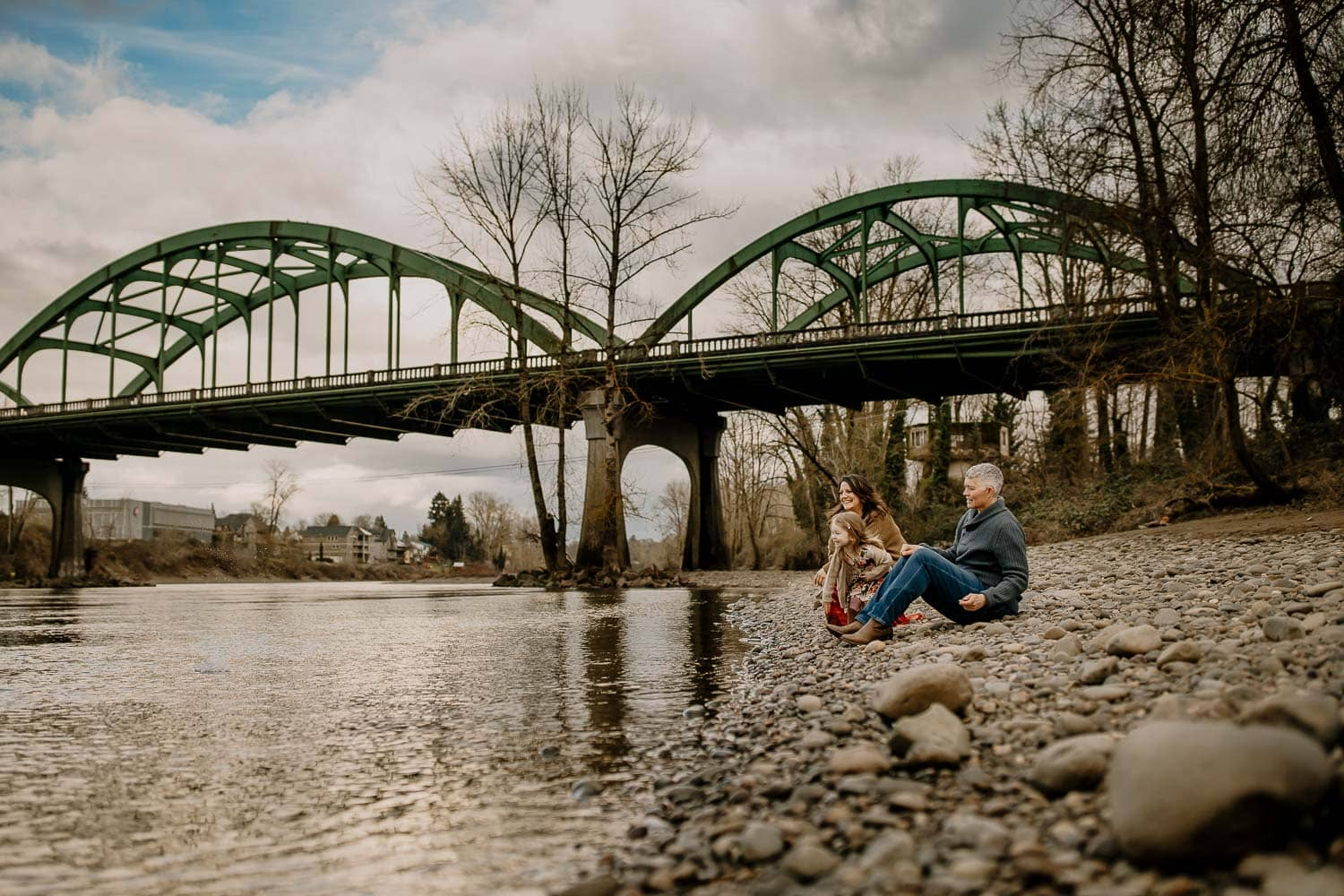 family of three sitting by a bridge throwing rocks into the river - top favorite tools for photography business