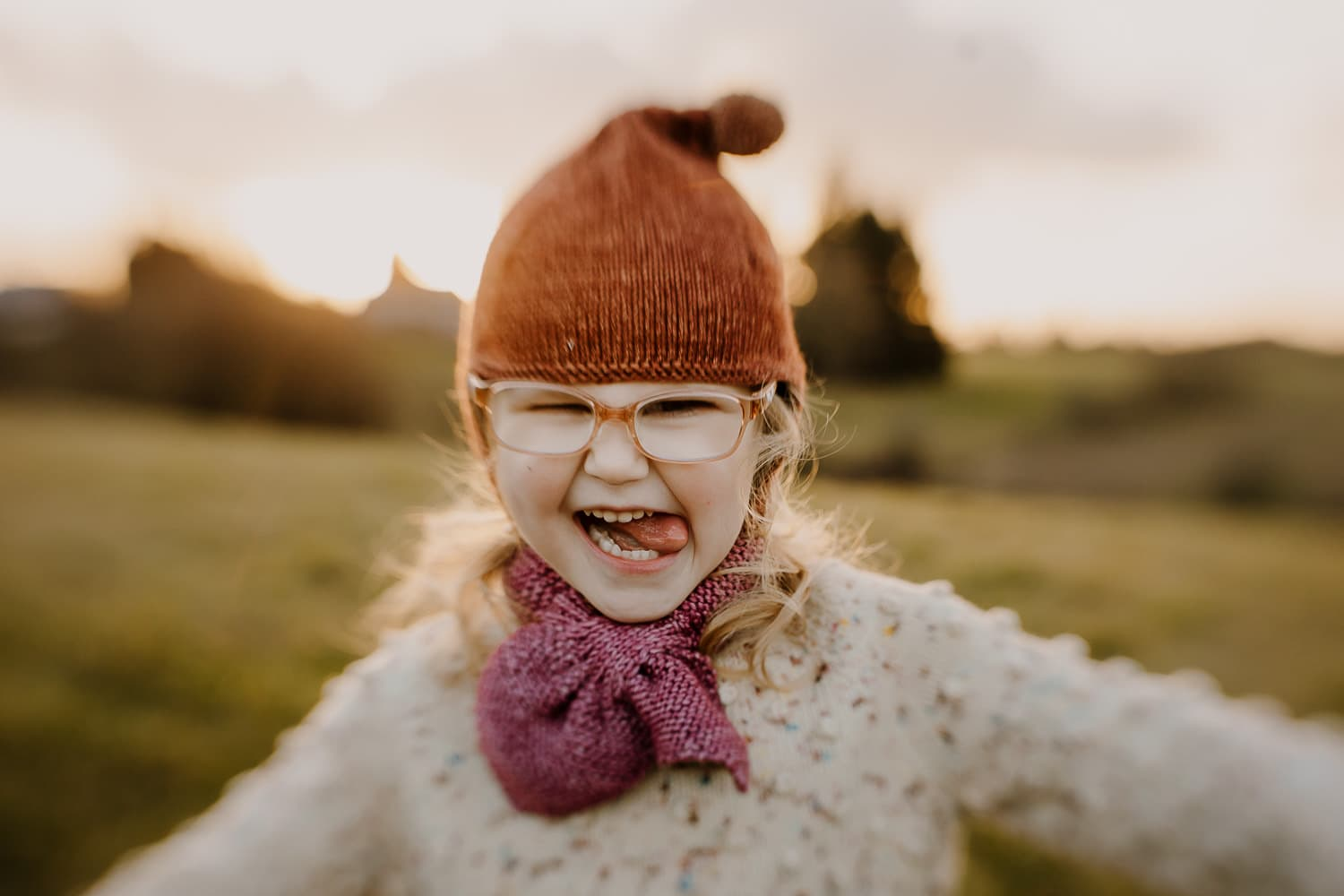 Toddler girl with her tongue sticking out, smiling - family photographer business tools