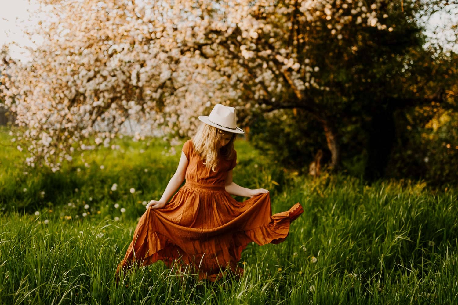 Preteen girl in an orange Joyfolie maxi dress with green grass and charry blossoms behind her - starting a photography business tips