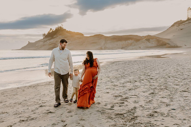 Oregon Coast Adventure Photographer - Family walking on the beach with Cape Kiwanda behind them