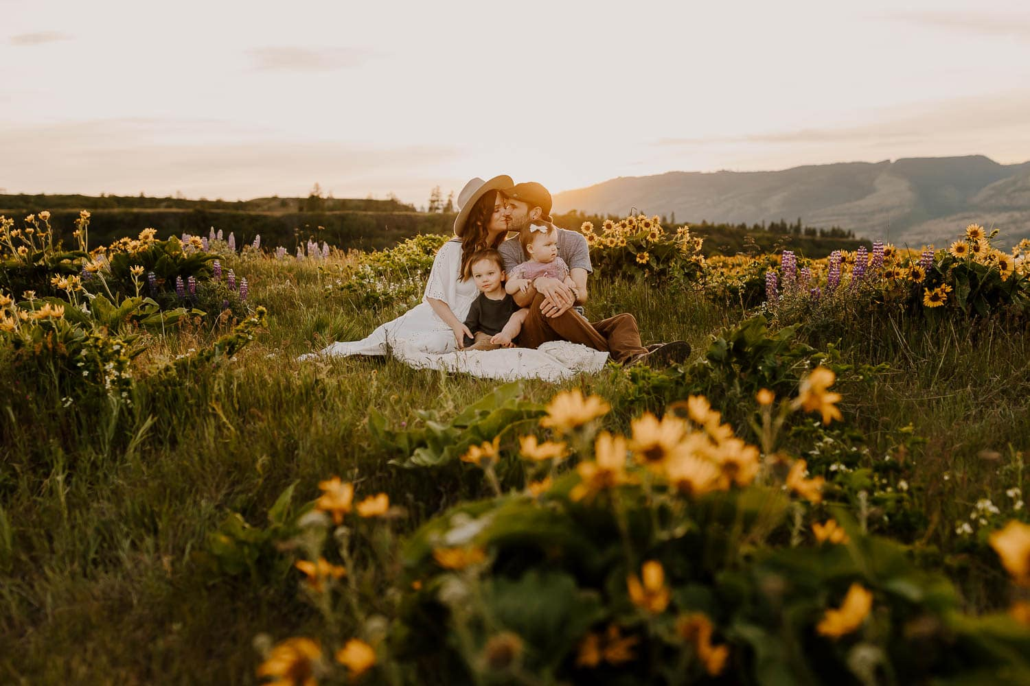 Family sitting on a blanket while parents kiss in the wildflowers in the gorge in spring