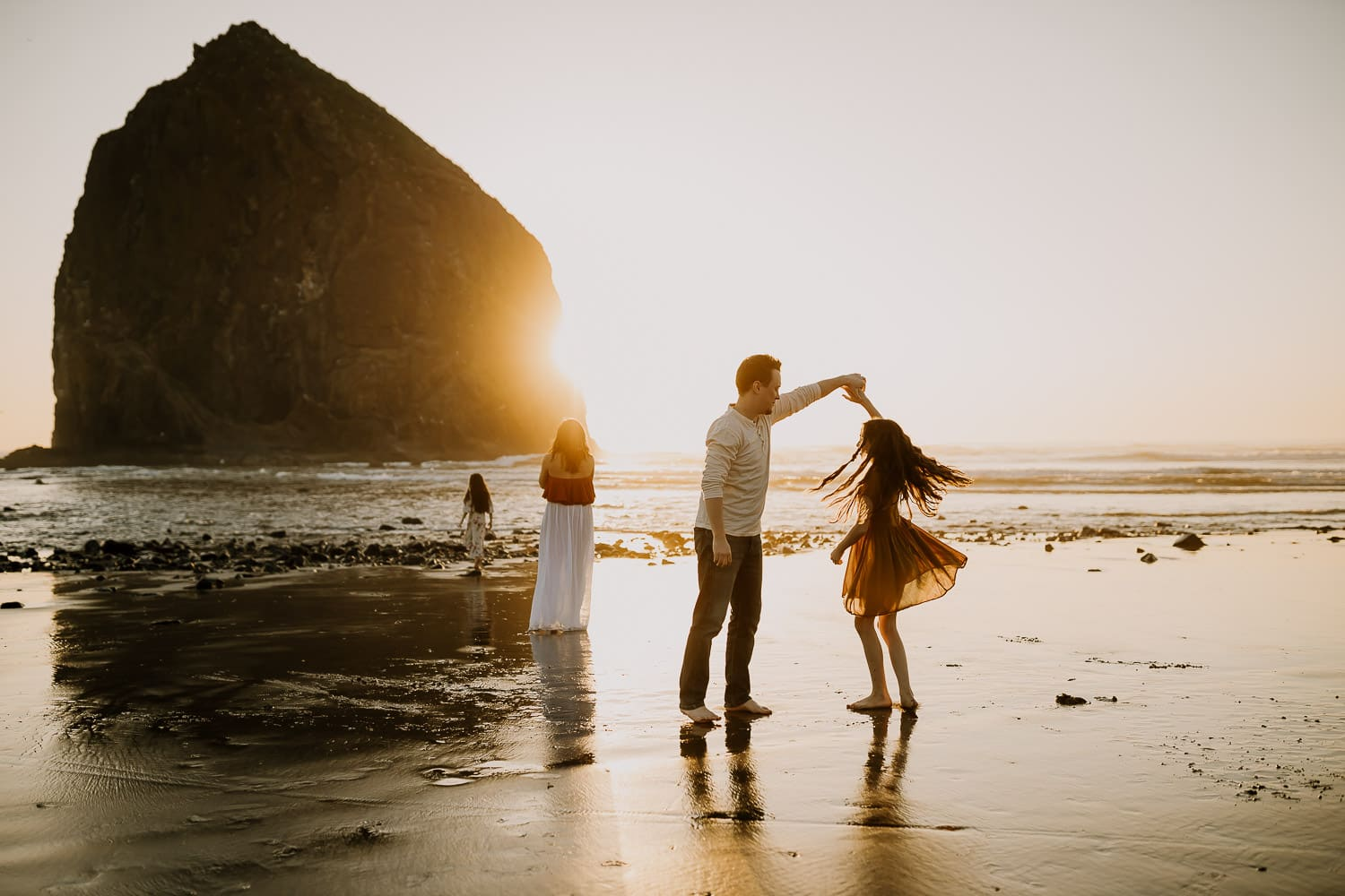 oregon coast photographer photos of family dancing together on the beach