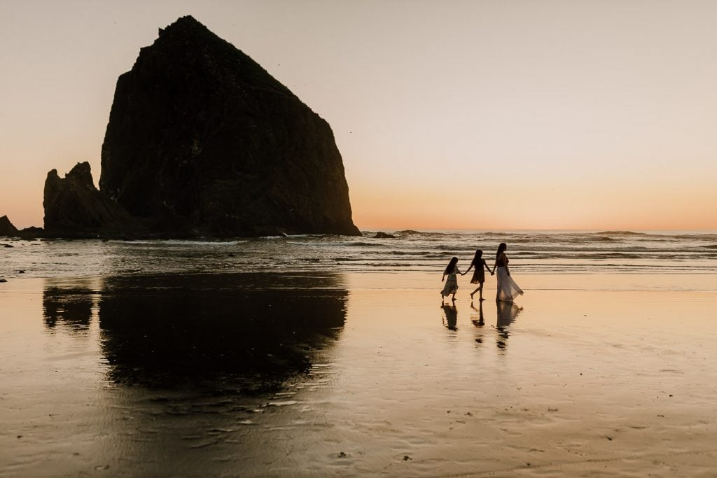 Mom walking with daughters at cannon beach