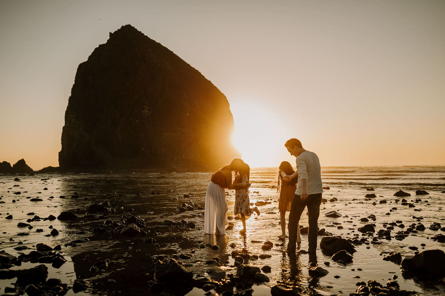 photo of a family playing on the beach with the golden sunset peeking past haystack rock