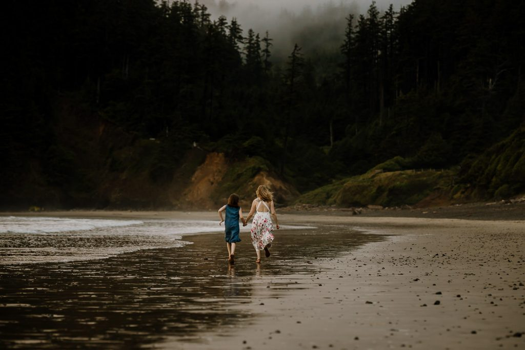 mom and daughter running along the coast while holding hands