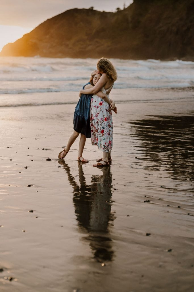 Mom hugging daughter at sunset near Seaside, Oregon during family vacation