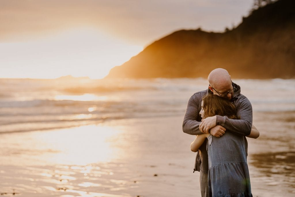 Dad and daughter hugging with the setting sun on the oregon coast