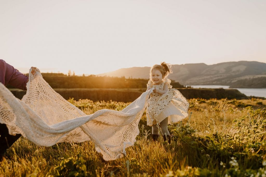 Toddler girl playing with blanket waving in the wind