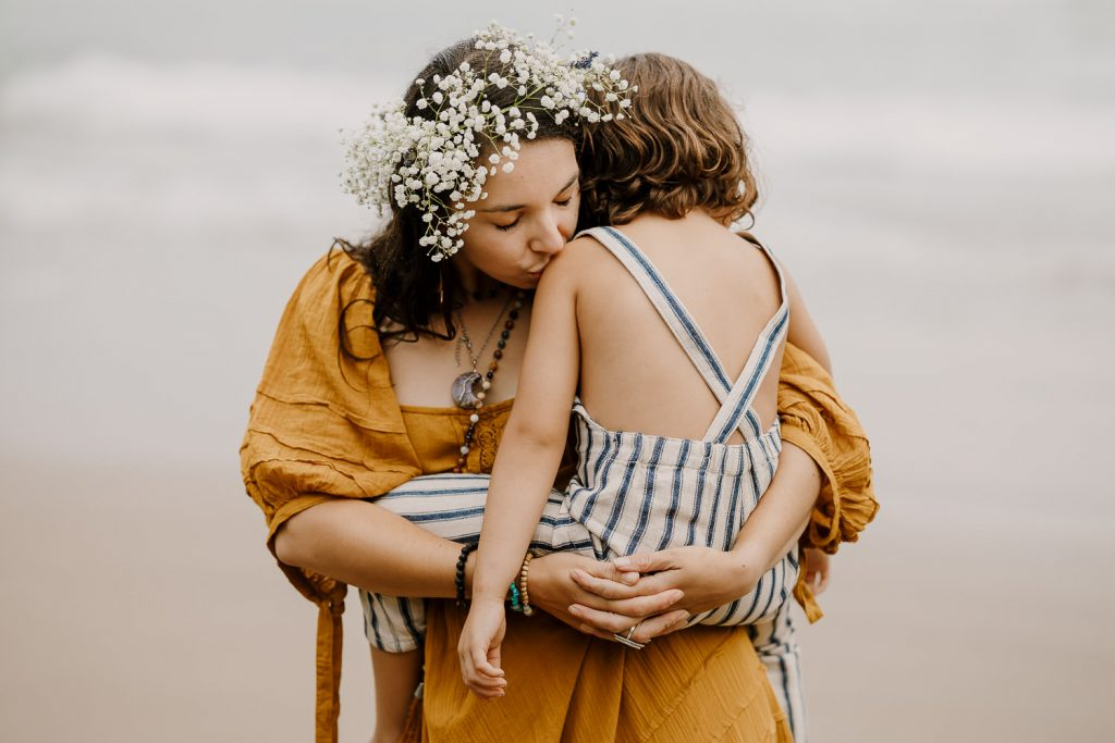 Mom kissing son's shoulder during family photos at Cannon Beach