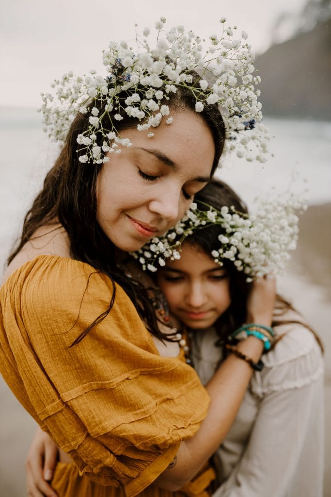 Mom hugging daughter close during family photos at the oregon coast