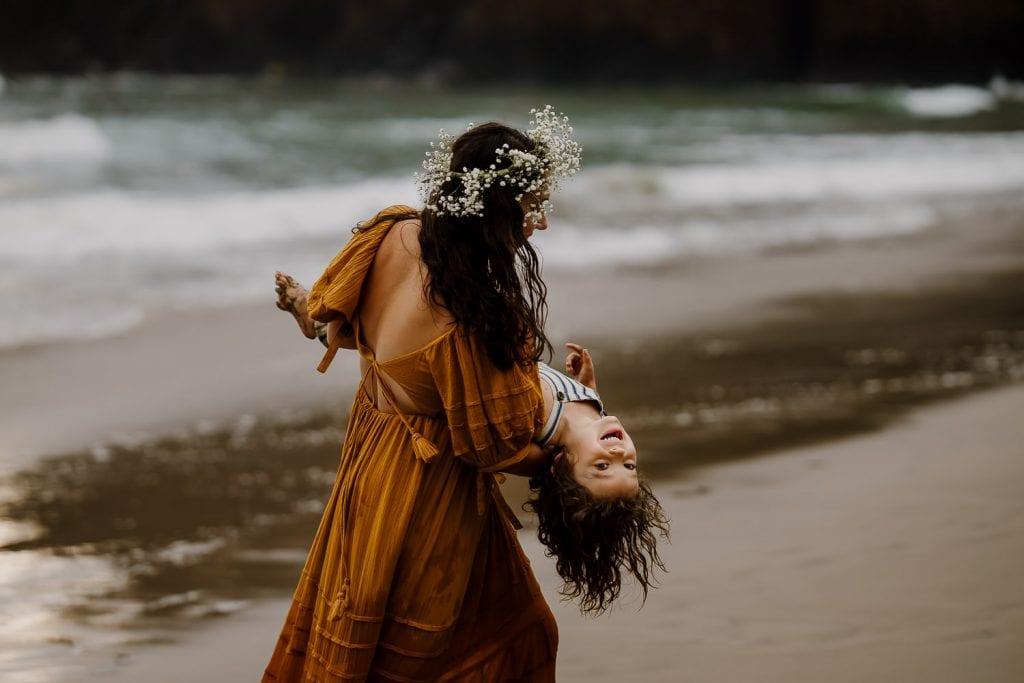 Mom spinning son around on the beach
