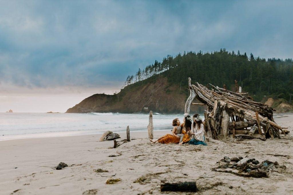 Family sitting beside a driftwood hut near Cannon Beach Oregon